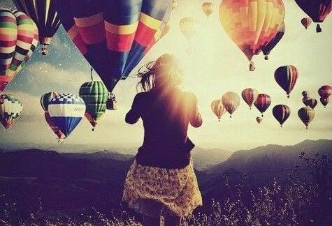 mujer ante paisaje con globos simbolizando las frases para aprovechar el día