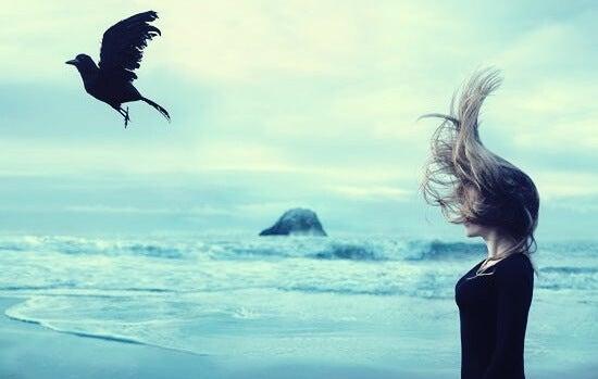 Chica ante un cuervo experimentando melancolía