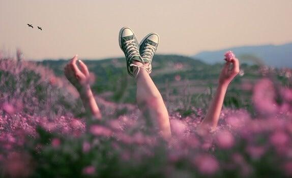 chica acostada en campo disfrutando de la felicidad en pequeños actos
