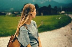 Chica que mira un camino intentando poner distancia