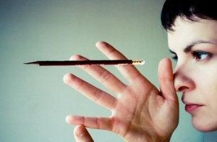 chica mirando un lápiz potenciando su cerebro creativo