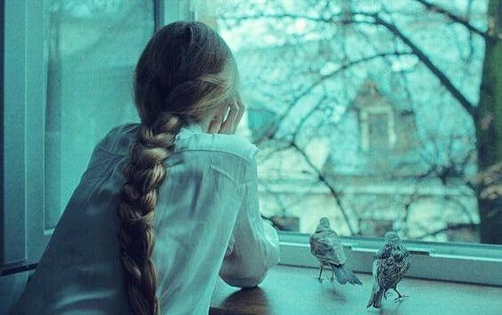 chica en la ventana con pájaros experimentando melancolía