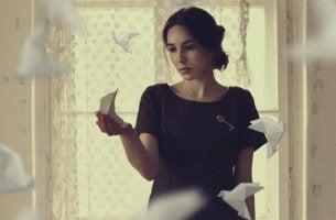 chica rodeada de pajaritas de papel que sufre heridas emocionales del pasado