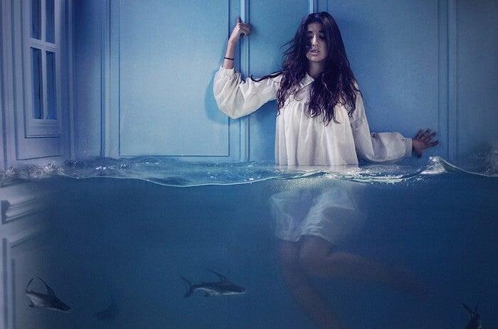 mujer en el agua rodeada de tiburones errados simbolizando el miedo que se disfraza de pereza