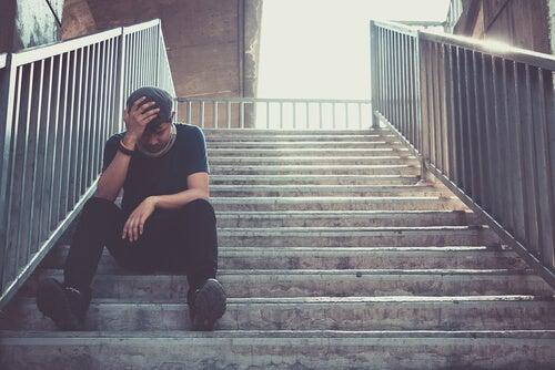 Chico en escaleras deprimido