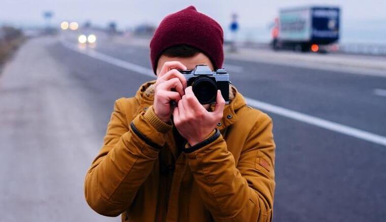 hombre haciendo fotos simbolizando cómo ser feliz, según la ciencia