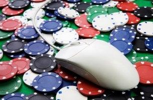 Ratón de ordenador sobre fichas de poker para representar la adicción a las apuestas online