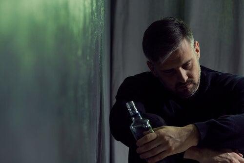 Hombre con botella de alcohol en la mano