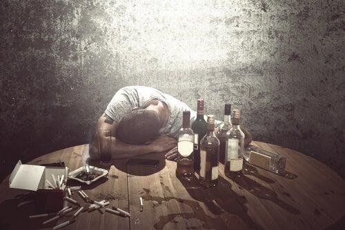 Hombre con la cabeza en la mesa y muchas botellas de alcohol