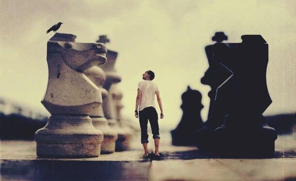 hombre entre piezas de ajedrez simbolizando que estás siendo conformista