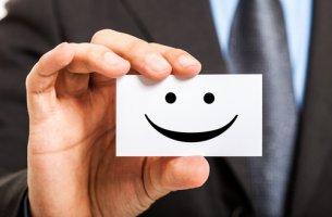 Hombre sujetando un cartel con una cara sonriendo