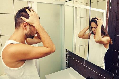 Hombre viéndose en el espejo como una mujer