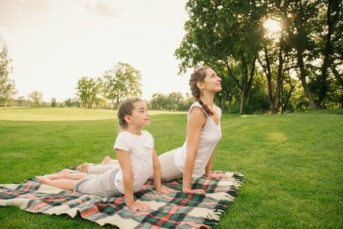 Madre haciendo con hija yoga