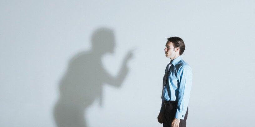 Sombra amenazando a un hombre simbolizando el efecto del síndrome de alta exposición