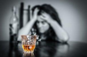 Mujer alcohólica con las manos en la cabeza para representar el trastorno por consumo de alcohol