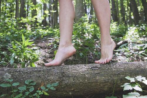 Mujer caminando por un tronco
