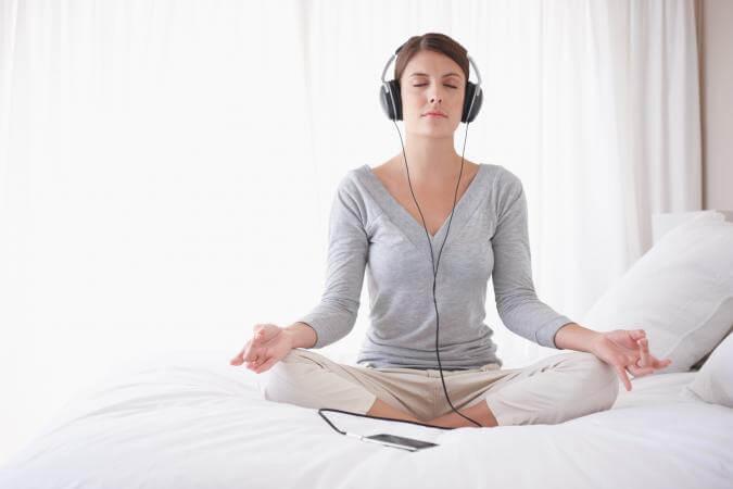 chica con auriculares practicando técnicas de relajación para dormir mejor