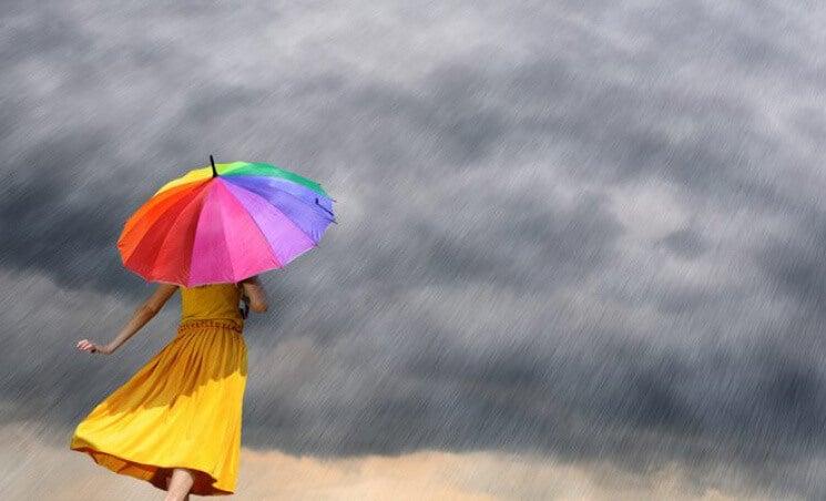 mujer con paraguas de colores afrontando la adversidad