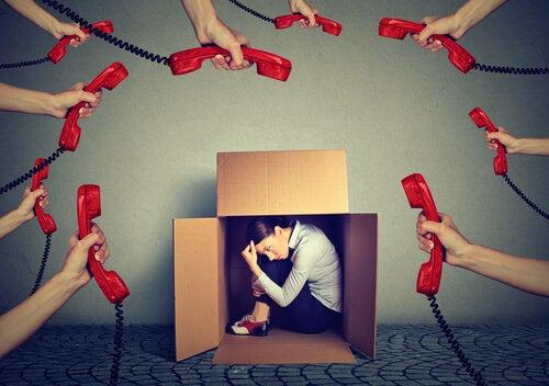 Mujer escondida en una caja con teléfonos alrededor