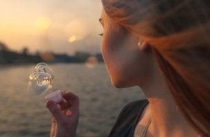 Mujer haciendo burbujas pensando en que disfrutamos poco de lo que tenemos