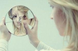 Mujer mirándose en un espejo con el cristal roto pensando cómo superar un defecto físico
