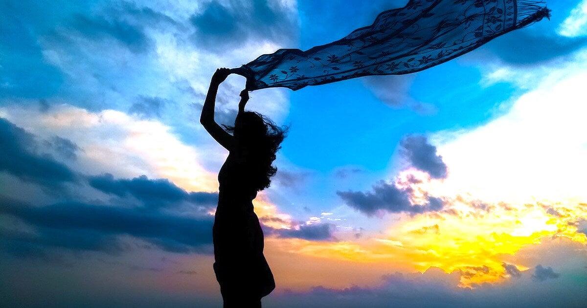 Chica con tela al viento simbolizando que importa cómo reaccionas