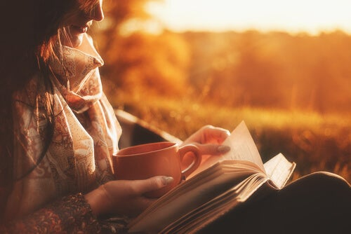 Mujer tomando un café y leyendo un libro