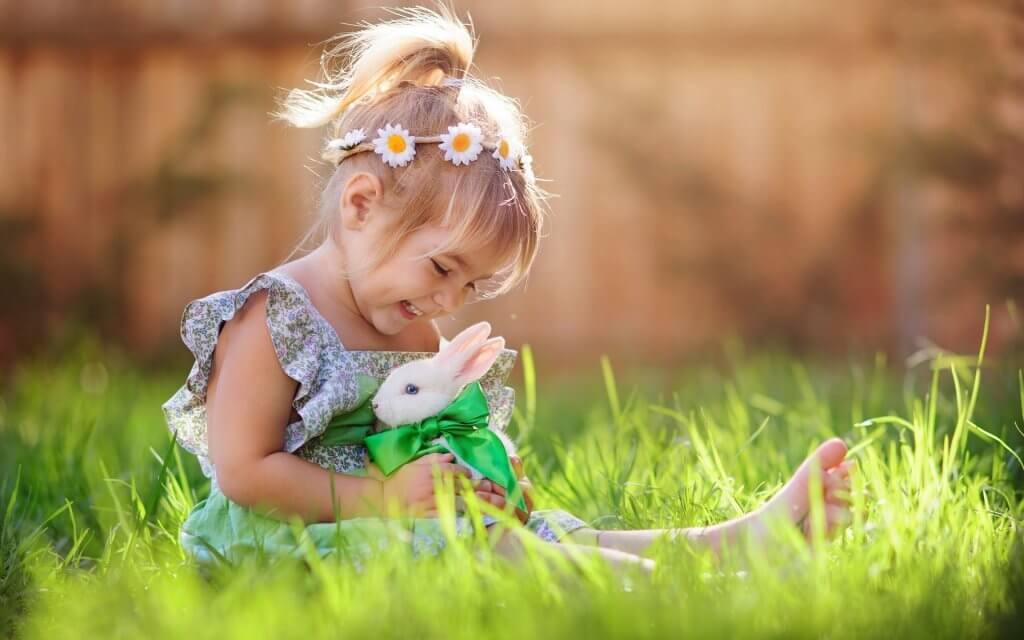 Niña con conejo en el campo