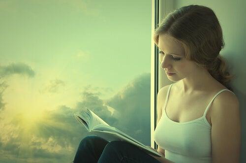 Niña leyendo un libro al lado de una ventana