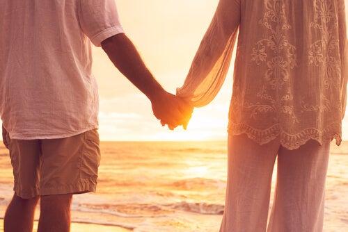 Pareja agarrada de la mano en la playa