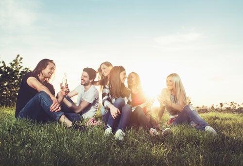 Amigos sentados en el cesped hablando