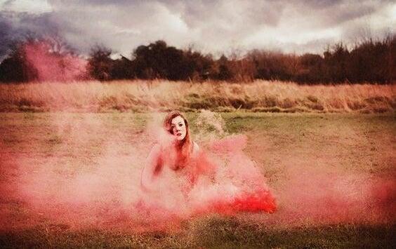 Chica en el campo envuelta en humo rosado haciéndose una pregunta dolorosa