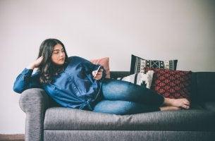 Chica en el sofá leyendo cómo evitar el sedentarismo