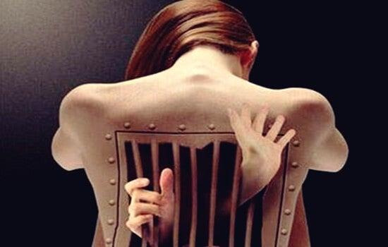mujer con cárcel imagen simbolizando cómo afectan las emociones a la espalda