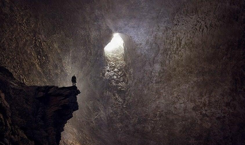 Hombre mirando gruta de salida tras haber tocado fondo