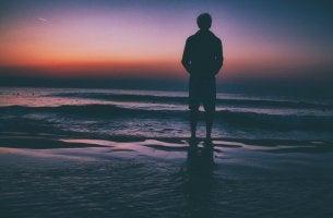 Hombre con síndrome de la soledad crónica frente al mar