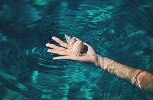 mano en el agua que sujeta caracol de mar simbolizando a alguien que busca aprender a priorizar