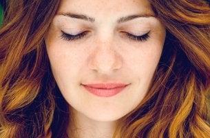 Mujer con los ojos cerrados mientras sonríe