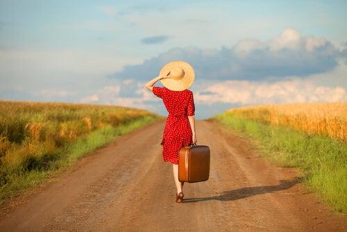 Mujer con maleta por un camino