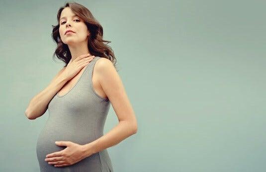 mujer tocándose el cuello simbolizando la tiroides y embarazo