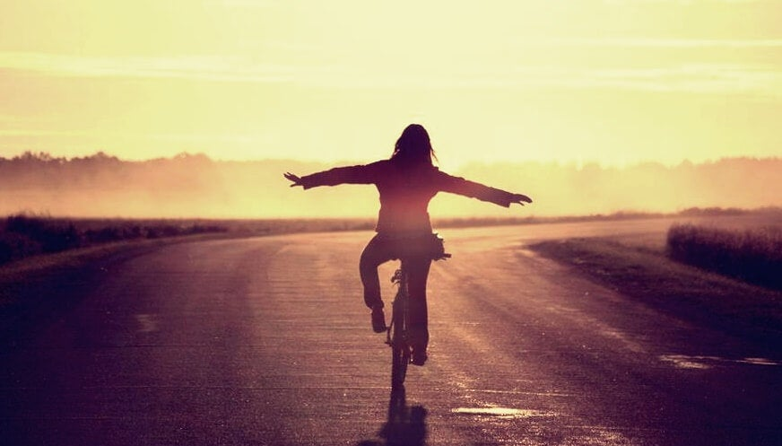 Mujer feliz en bicicleta por aplicar el masturdating