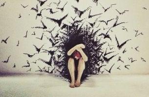 mujer envuelta en pájaros sufriendo el efecto de los tomadores emocionales