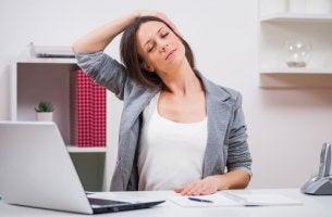 Mujer haciendo estiramientos de cuello en la oficina para representar los ejercicios de pausas activas