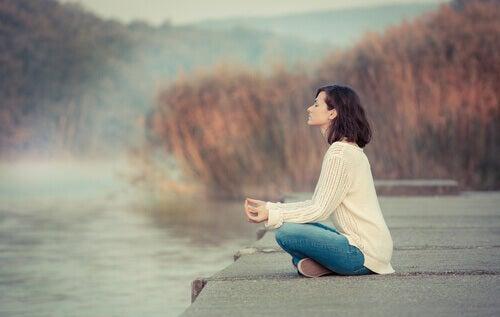 Mujer haciendo mindfulness cerca de un lago