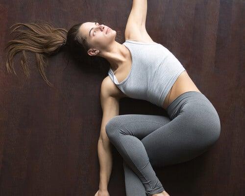 Mujer haciendo postura del giro espinal