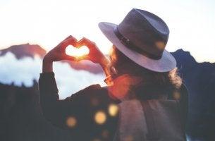 Mujer haciendo un corazón con las manos para representar las libertades de Virginia Satir
