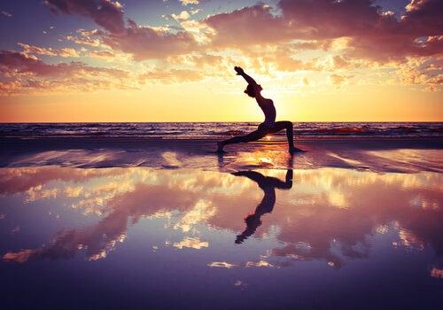 Mujer haciendo yoga al atardecer para representar una de las sendas del yoga