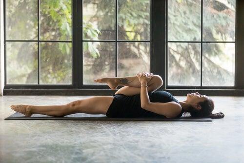 Mujer tumbada en el suelo llevándose una rodilla al pecho