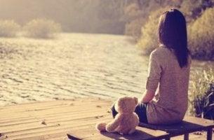 Niña sentada en un banco con un osito