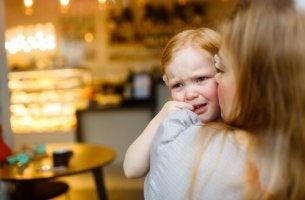 Niña pequeña llorando en brazos de su madre